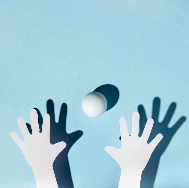 Bovenaanzicht van papieren handen met pingpongbal