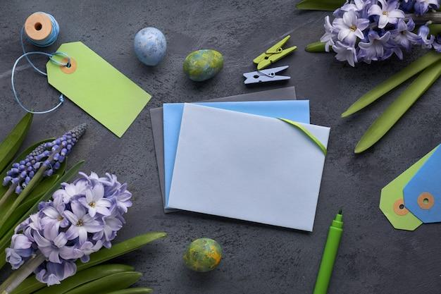 Bovenaanzicht van papieren kaarten met kopie-ruimte, blauwe hyacint bloemen en paaseieren op donker
