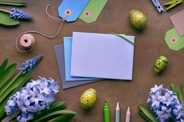 Bovenaanzicht van papieren kaarten met kopie-ruimte, blauwe hyacint bloemen en paaseieren op donkere achtergrond, tekst