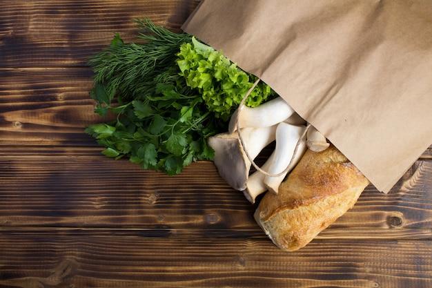 Bovenaanzicht van papieren zak met voedsel op de houten achtergrond
