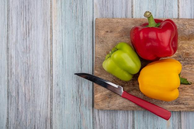 Bovenaanzicht van paprika en mes op snijplank op houten achtergrond met kopie ruimte