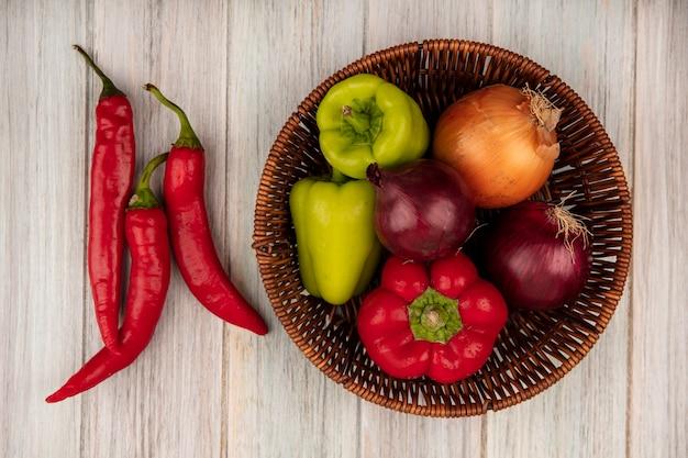 Bovenaanzicht van paprika op een emmer met uien met chilipepers geïsoleerd op een grijze houten achtergrond