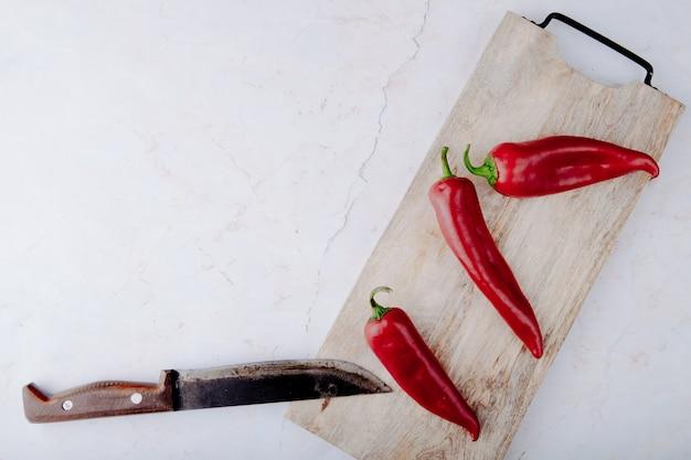 Bovenaanzicht van paprika op snijplank met mes op witte achtergrond met kopie ruimte
