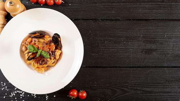 Bovenaanzicht van pasta en zeevruchten op houten tafel