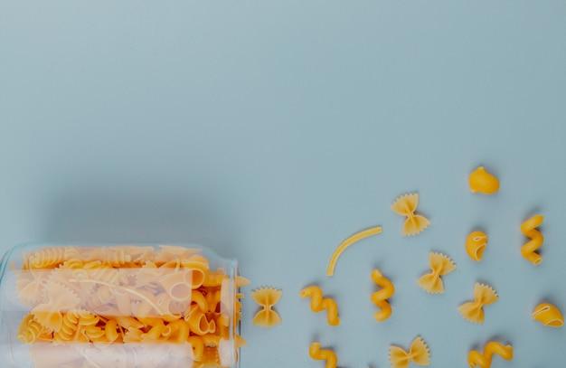 Bovenaanzicht van pasta morsen uit pot op blauwe ondergrond