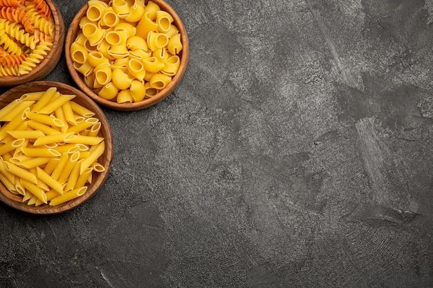 Bovenaanzicht van pasta samenstelling rauwe producten binnen platen op grijs