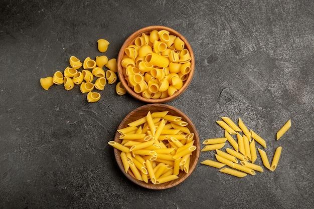 Bovenaanzicht van pasta samenstelling verschillende gevormde rauwe italiaanse pasta binnen platen op grijs