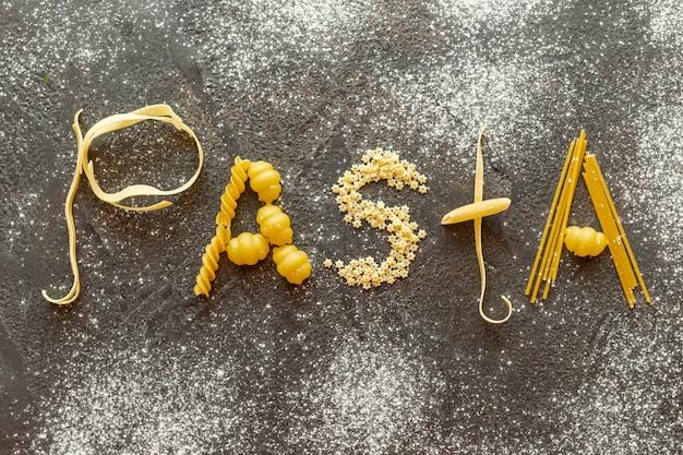 Bovenaanzicht van pasta woord op effen achtergrond