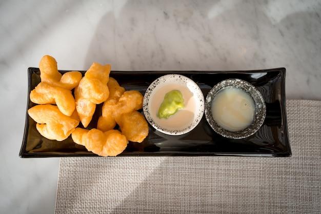 Bovenaanzicht van patonggo of gefrituurde deegsticks op zwarte schaal met pandan en zoete condensmelk op tafel, thais ontbijt
