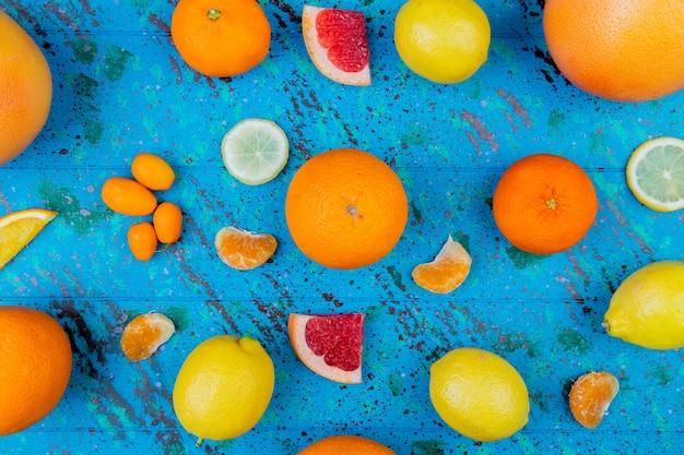 Bovenaanzicht van patroon van citrusvruchten als oranje citroen mandarijn kumquat grapefruit op blauwe tafel