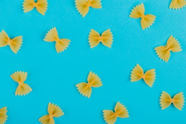 Bovenaanzicht van patroon van farfalle pasta op blauwe ondergrond