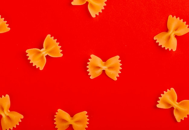 Bovenaanzicht van patroon van farfalle pasta op rode ondergrond