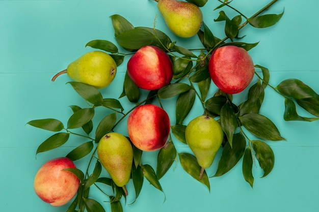 Bovenaanzicht van patroon van fruit als peer en perzik met bladeren op blauwe achtergrond