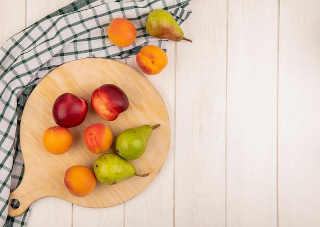 Bovenaanzicht van patroon van fruit als perzik abrikoos en peer op snijplank en op geruite doek op houten achtergrond met kopie ruimte