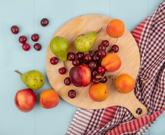 Bovenaanzicht van patroon van fruit als perzik, peer, abrikoos kers op snijplank op geruite doek en op blauwe achtergrond