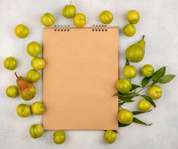 Bovenaanzicht van patroon van fruit als pruimen en peer met bladeren rond notitieblok op witte achtergrond met kopie ruimte