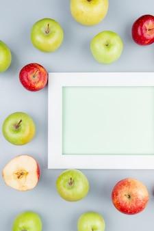 Bovenaanzicht van patroon van gesneden en hele appels rond bord op grijze achtergrond met kopie ruimte