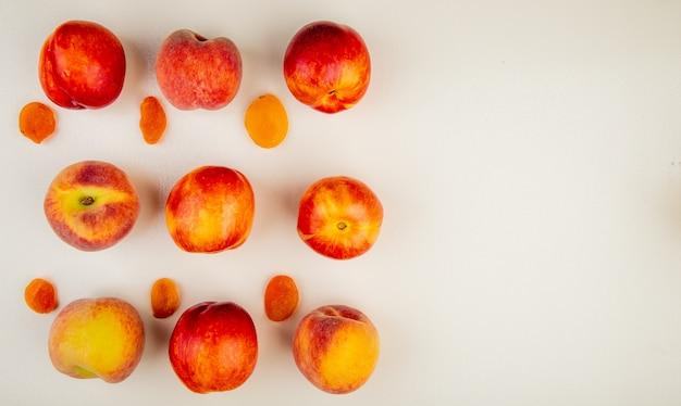 Bovenaanzicht van patroon van gesneden en hele perziken aan linkerkant en wit oppervlak met kopie ruimte