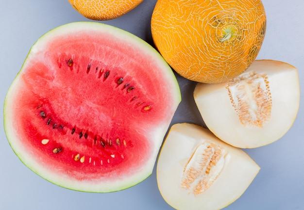 Bovenaanzicht van patroon van gesneden en hele vruchten als watermeloen en meloen op blauwachtig grijze achtergrond