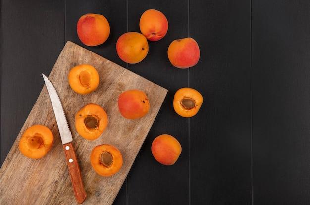Bovenaanzicht van patroon van half gesneden abrikozen met mes op snijplank en hele degenen op zwarte achtergrond met kopie ruimte