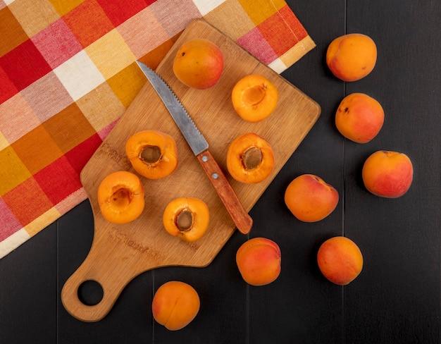 Bovenaanzicht van patroon van half gesneden abrikozen met mes op snijplank op geruite doek en hele op zwarte achtergrond