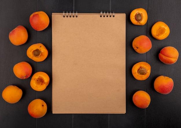 Bovenaanzicht van patroon van hele en halve gesneden abrikozen en notitieblok op zwarte achtergrond met kopie ruimte