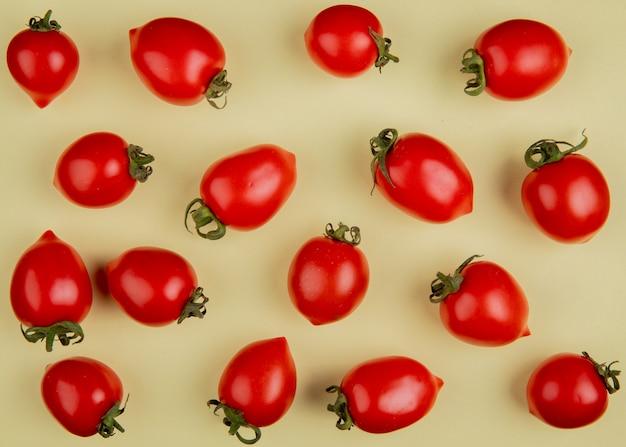 Bovenaanzicht van patroon van tomaten op gele ondergrond