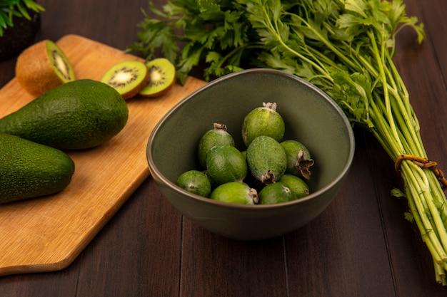 Bovenaanzicht van peervormige avocado's op een houten keukenbord met plakjes kiwi met feijoas op een kom met peterselie geïsoleerd op een houten oppervlak