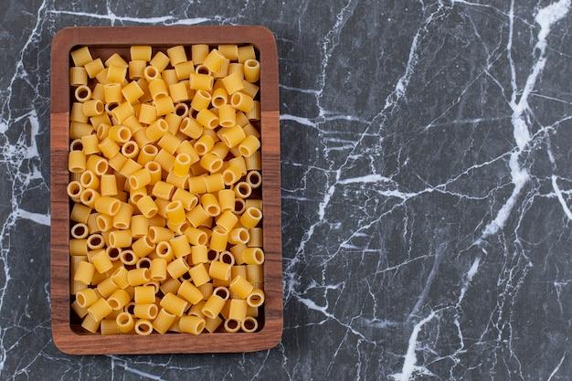Bovenaanzicht van penne pasta op een houten bord over zwart.