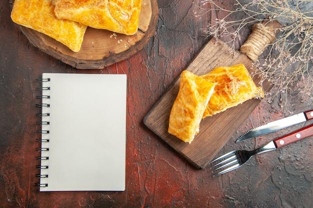 Bovenaanzicht van penovani khachapuri op houten bord en op snijplank met mes en vork een notitieboekje op donkerrood oppervlak