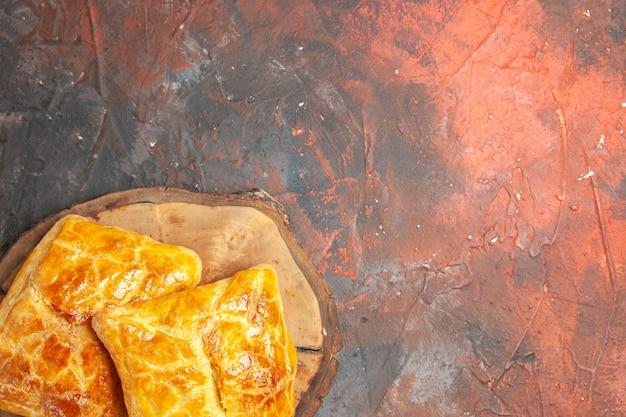 Bovenaanzicht van penovani khachapuri op houten bord op donkerrood oppervlak