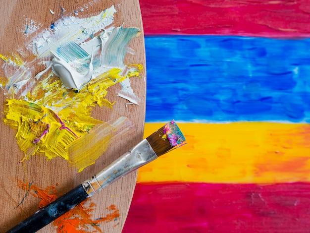 Bovenaanzicht van penseel met verf en palet