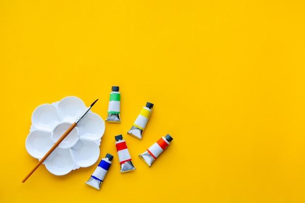 Bovenaanzicht van penselen, kleurenbuizen en palet