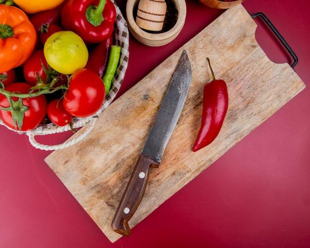 Bovenaanzicht van peper en mes op snijplank met groenten in mand en knoflook crusher op bordo oppervlak
