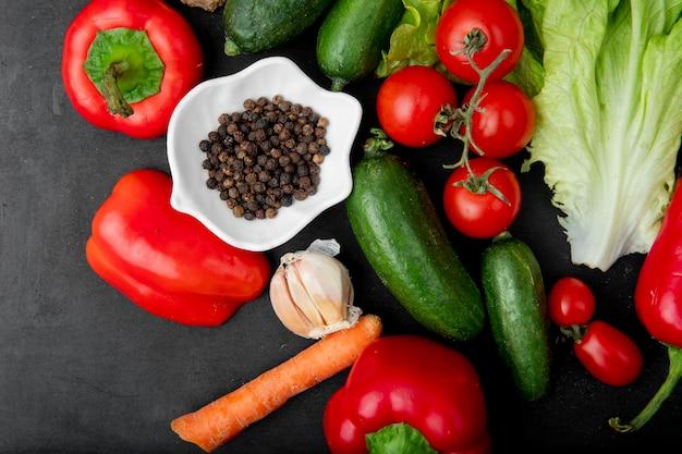 Bovenaanzicht van peper ruimte met peper komkommer knoflook wortel en andere groenten op zwarte achtergrond