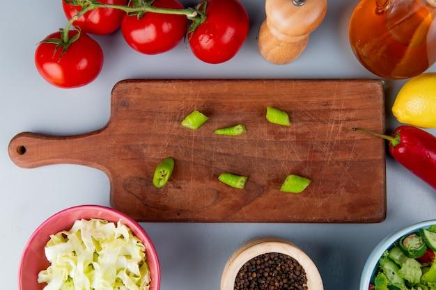 Bovenaanzicht van peper segmenten op snijplank met kool plakjes tomaten plantaardige salade zwarte peper zaden boter citroen op blauwe achtergrond
