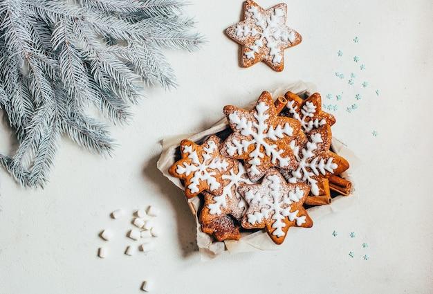 Bovenaanzicht van peperkoek kerstkoekjes in de vorm van sneeuwvlokken met slagroom naast takken van een kerstboom op een witte achtergrond