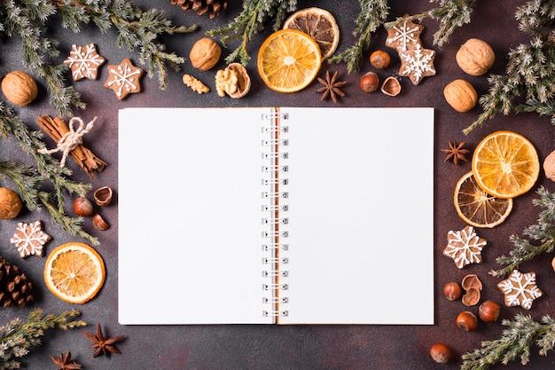 Bovenaanzicht van peperkoekkoekjes met dennenappels en notitieboekje Premium Foto