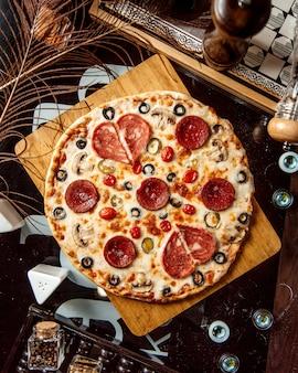 Bovenaanzicht van pepperoni pizza met olijf champignons en kaas