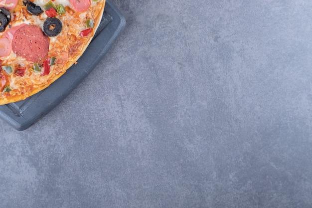 Bovenaanzicht van pepperoni pizza op grijze achtergrond.