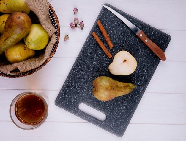 Bovenaanzicht van peren segment met kaneelstokjes en keukenmes op een zwarte snijplank een rieten mand met rijpe peren en een glas limonade op witte houten achtergrond