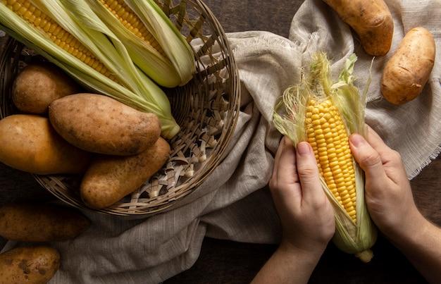 Bovenaanzicht van persoon maïs pellen met aardappelen
