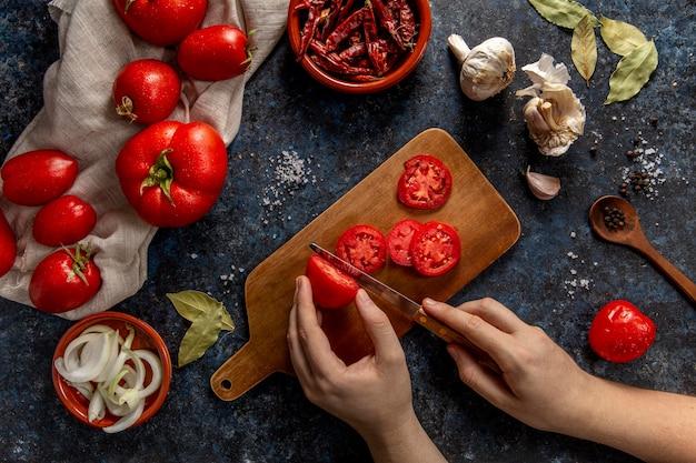 Bovenaanzicht van persoon snijden tomaten met chili