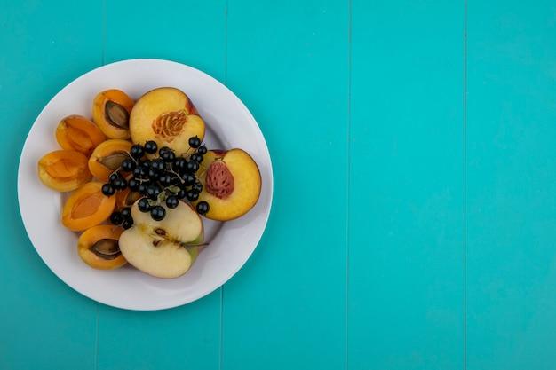 Bovenaanzicht van perzik met abrikozen en een appel met zwarte bessen op een bord op een lichtblauw oppervlak