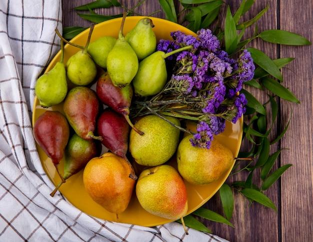 Bovenaanzicht van perziken en bloemen in plaat op geruite doek en houten oppervlak versierd met bladeren