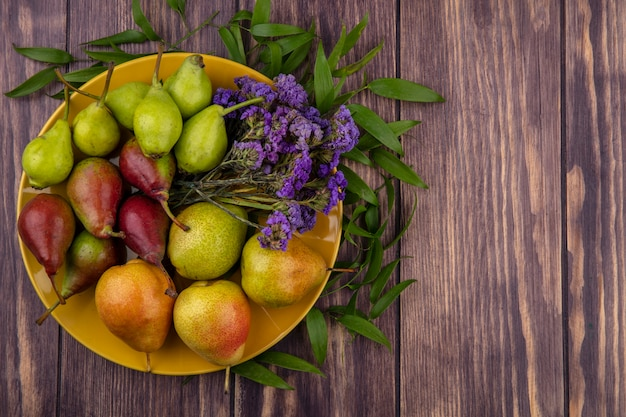 Bovenaanzicht van perziken en bloemen in plaat op houten oppervlak