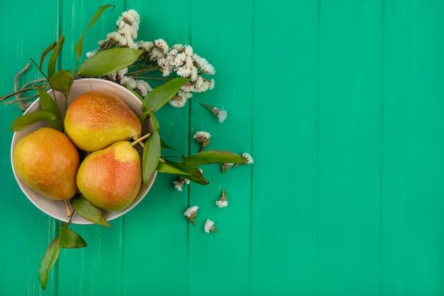 Bovenaanzicht van perziken in kom met bloemen op groene ondergrond