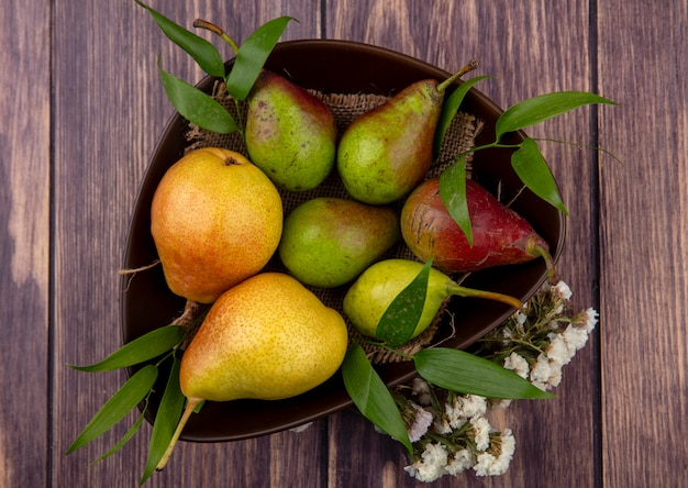 Bovenaanzicht van perziken in kom met bloemen op houten oppervlak