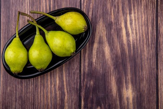 Bovenaanzicht van perziken in langwerpige plaat op houten oppervlak