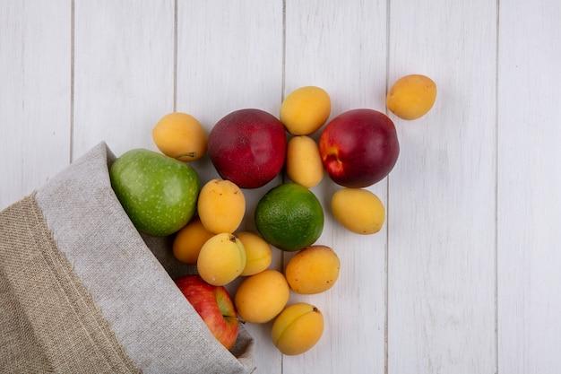 Bovenaanzicht van perziken met appels en abrikozen in een jutezak op een wit oppervlak